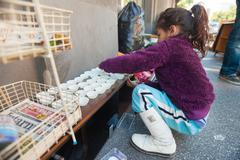 Little Roma girl playing with cupcake molds at street garbage dump. Stock Photos