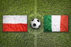 Poland vs. Italy flags on soccer field - stock photo