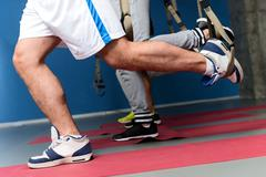 Strong sportsmen exercising in gym Stock Photos