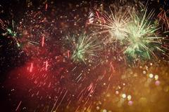 Abstract holiday background, glitter lights and firework overlay. Stock Photos