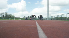4K Disabled athletes in racing wheelchairs training together at race track Stock Footage