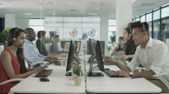 4K Friendly financial advice team taking calls in busy call center - stock footage