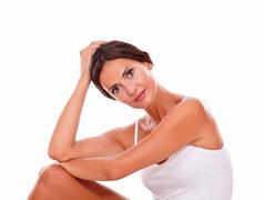 Attractive woman with her knee up and her hand to head while looking at camer Stock Photos