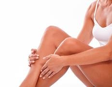 Female body with knees bent sitting down and holding hands on calves while we Stock Photos