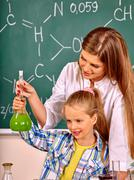 Child girl and teacher holding flask in chemistry class. - stock photo