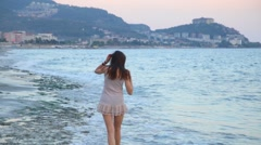 Beautiful girl on the beach alone walking by coastline. Travel concept. Stock Footage