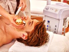 Young man receiving electric facial massage. - stock photo