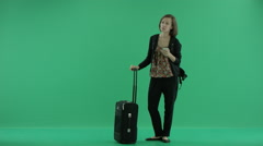 Female tourist with suitcase stands talking on the phone Stock Footage