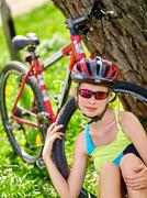Bikes cycling girl wearing helmet have rest sitting under tree. Stock Photos