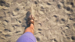 A man walks in flip flops on the sand near the sea Stock Footage