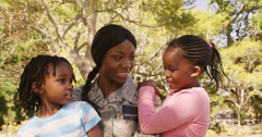 Soldier mother holding her two children in a park Stock Footage