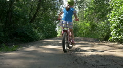 Little girl rides a bike on nature, back view, slow motion Stock Footage
