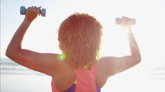 Fit Ethnic African American female with dumbbells weights doing arm raises  Stock Footage