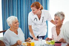 Smiling nurse looking at senior person during breakfast in a retirement home - stock photo