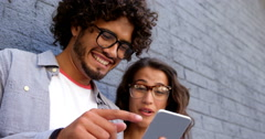 Friends smiling while looking at smartphone Stock Footage