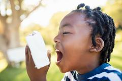 Child using asthma object at park - stock photo