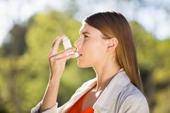 Woman using asthma inhaler in a park - stock photo