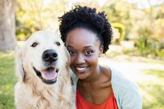 Woman posing with a dog at park - stock photo