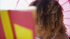 Afro hair African American female laughing and happy reading a literature book Stock Footage