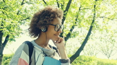 Pretty african girl listening to music on a sunny day in the park - stock footage