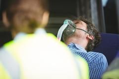 Close-up of an injured man wearing oxygen mask on a stretcher - stock photo