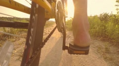 Man rides a bike on a country road, sunbeams in the lens,  slow motion Stock Footage