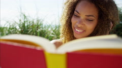Portrait of relaxed plus size Ethnic African American female reading a book Stock Footage