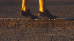 CU shot of teen walking on the road curb Stock Footage
