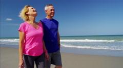 Active senior Caucasian couple enjoying walking on the beach Arkistovideo