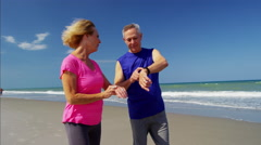 Active mature Caucasian couple enjoying exercise on the beach Stock Footage