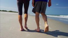 Feet of mature Caucasian couple enjoying walking on the beach Stock Footage