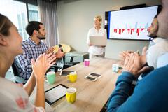 Coworkers applauding a colleague after presentation in the conference room Stock Photos