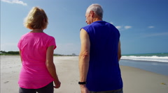 Caucasian seniors enjoying walking on the ocean beach Stock Footage