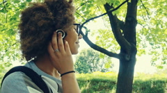 Lovely girl smiling and is happy listening to music with headphones in the park Stock Footage