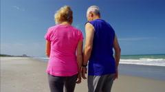 Mature Caucasian couple enjoying fitness activity on beach vacation Stock Footage