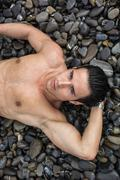 Young shirtless athletic man laying down on pebbles Stock Photos