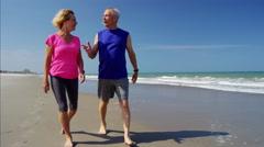 Senior Caucasian couple enjoying exercise on the beach Stock Footage