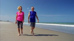 Active mature Caucasian couple keeping fit on the beach Stock Footage