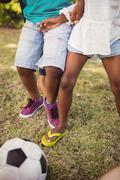Zoom on family playing football at park - stock photo