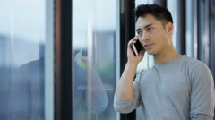 4K Businessman standing next to window & talking on cell phone in city office - stock footage