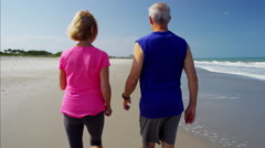 Happy senior Caucasian couple enjoying fitness activity on the beach Stock Footage