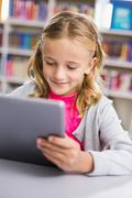 Schoolgirl using digital tablet in library at school - stock photo