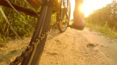 Man rides a bike on a country road, sunbeams in the lens, low point shooting Stock Footage