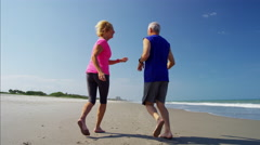 Caucasian seniors keeping fit running on the beach Stock Footage