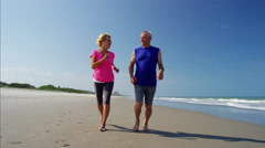 Active senior Caucasian couple enjoying jogging on the beach Stock Footage