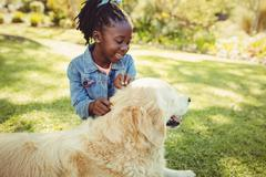 Girl posing with her dog at park - stock photo