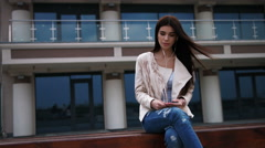 Young brunette woman sitting on a bench in the city, listening to music with Stock Footage