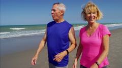 Active senior Caucasian couple keeping fit on the beach Arkistovideo
