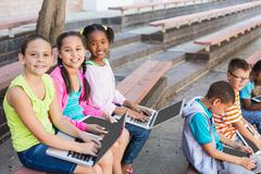 Smiling kids sitting on bench and using laptop at school Stock Photos