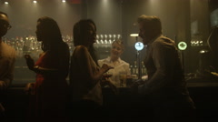 4K Young group socializing in nightclub & funny astronaut blending in with crowd Stock Footage